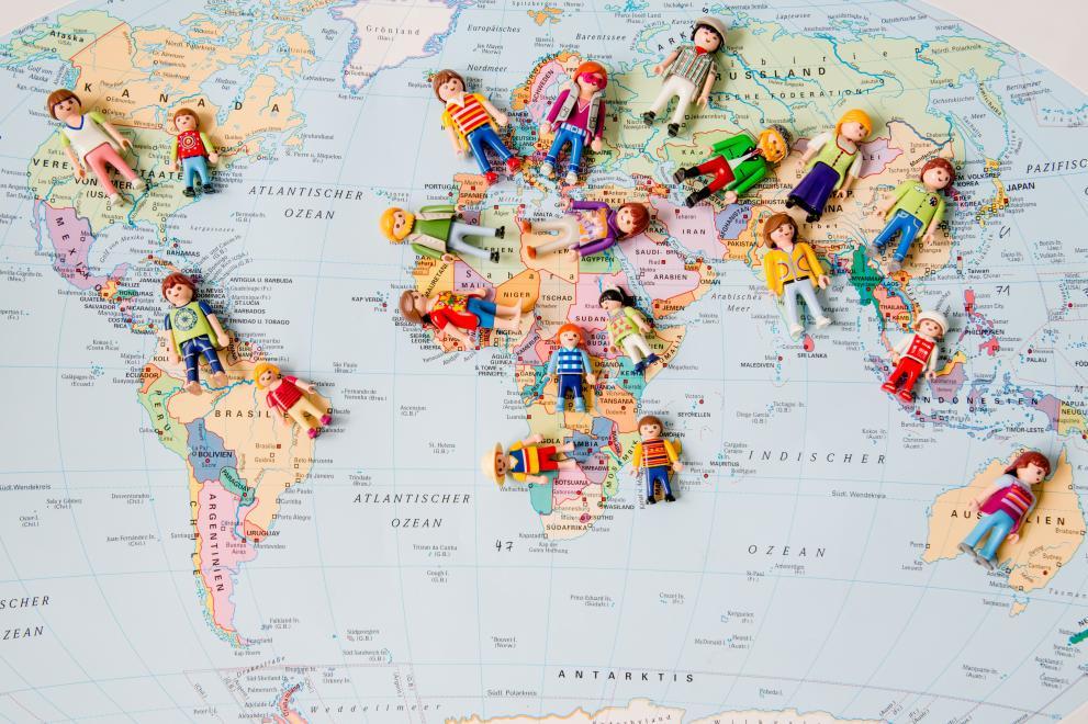 Weltkarte mit liegenden Playmobilfiguren auf den Kontinenten